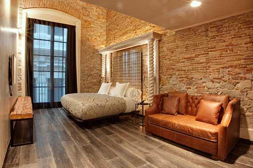 Habitación del Aparthotel Arai cuya cama cuenta con una cabecera de baldosas hidráulicas del S.XIX